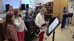 Lapset soittavat ja laulavat koulun oppitunnilla.