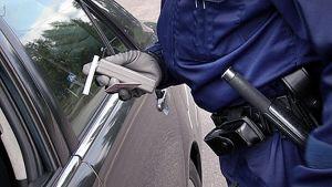 Poliisi pitelee alkometria ja ajokorttia ratsian aikana.