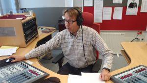 Radion toimittaja istuu studiossa äänipöydän äärellä