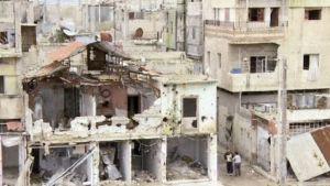 Vaurioituneita taloja Homsin kaupungissa.