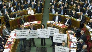 Opposition kansanedustajat pitelevät parlamentin istuntosalissa julisteita, joissa kehotetaan äänestämään uutta perustuslakia vastaan.
