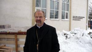 Kirkkoherra Elias Huurinainen seisoo Iisalmen Evakkokeskuksen edessä.
