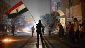 Mielenosoittaja heiluttaa Egyptin lippua Muslimiveljeskunnan päämajan edustalla Kairossa.