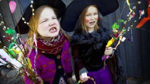 Kaksi pääsiäisnoidiksi pukeutunutta tyttöä virpomassa.