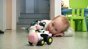 Lapsi makoilee lattialla ja leikkii lelulla.