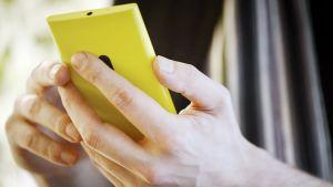 Mies selaa Nokia Lumia 920 -älypuhelinta.