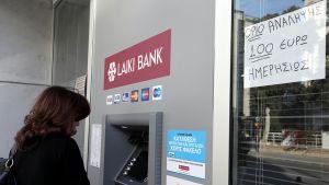 Nainen kyproslaisen Laiki-pankin automaatilla.