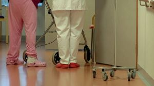 Vanhuksen ja hoitajan jalat hoitolaitoksen käytävällä