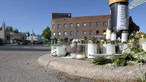 Muistokynttilöitä, kukkia ja viestejä jätettynät kadulle.