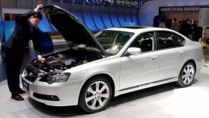 Toimittaja tutki Subaru Legacy -mallin autoa Geneven automessuilla.