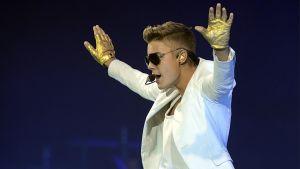 Justin Bieber esiintyy valkoisissa kultaiset sormikkaat käsissä.