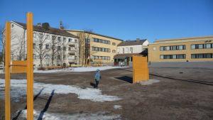 Koulurakennuksia ja lapsi koulun pihalla.