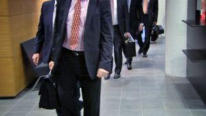 Miehiä puvuissaan kävelee käräjäoikeuden käytävällä kohti oikeussalia.