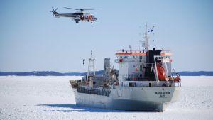 Rahtilaiva Nordanvik ja sen yllä kiertelevä rajavartiolaitoksen helikopteri.