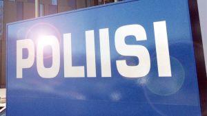 Poliisi-kyltti auringonloisteessa.
