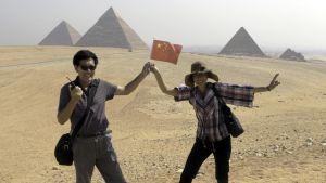 Kiinalainen pari pyramidien edessä.