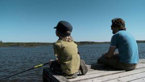 Kai ja pieni poika järven äärellä. Lokki lentää sinisellä taivaalla.