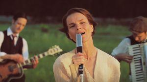 Laulaja Anna Järvinen musisoi laskevan auringon punertavassa valossa.