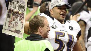 Baltimore Ravensin Brendon Ayanbadejo pitää lehteä, jossa joukkueen julistetaan voittaneen Super Bowlin.