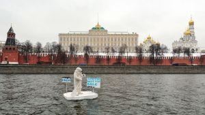 Jääkarhupukuinen henkilö meloo Kremlin edustalla.