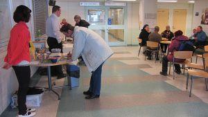 Ihmisiä terveyskeskuksen aulassa