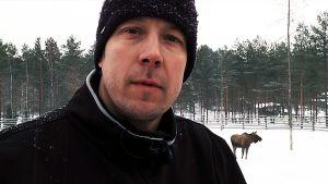 Erätulilla-ohjelman juontaja Mikko Peltsi Peltola seisoo Ähtärin eläinpuistossa hirviaitauksessa, hirvi seisoo taustalla.