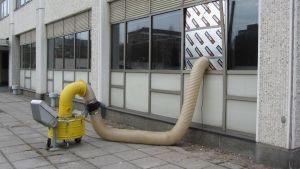 Kuvassa alipainetuuletin rakennuksen ulkopuolella ja sisään johtava letku
