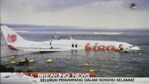 Takaosasta katkennut matkustajakone matalassa vedessä.