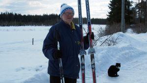 Kuvassa Aili Helminen suksiensa kanssa lumisella pihalla. Kuvassa myös kissa