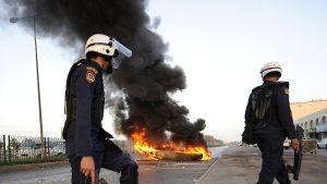 Bahrainilaiset mellakkapoliisit katselevat mielenosoittajien tiesuluksi sytyttämää romuvenettä.