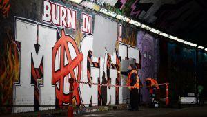 Työntekijät maalaavat piiloon Margaret Thatcherin vastaista seinämaalausta Lontoossa.