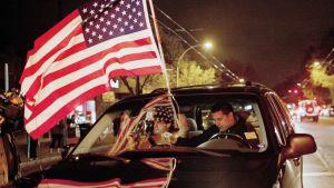 Nuoret miehet ajavat Yhdysvaltain lippu liuhuen auton katolla Bostonissa.
