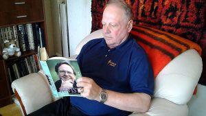 Pauli Salminen lukee kirjaa nojatuolissa.