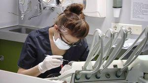 Suuhygienistiopiskelija hoitaaa potilasta hammashoitolassa.