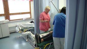 Kuvassa kaksi hoitajaa hoitaa potilasta yhteispäivityksessä.