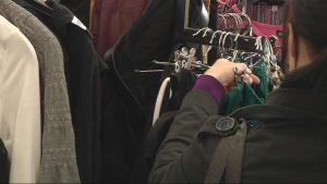 Nainen katsoo vaatteita kirpputorilla.