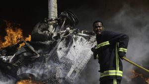 Palomies yrittää sammuttaa pommi-iskussa tuhoutuneita autoja Mogadishussa 5. toukokuuta.