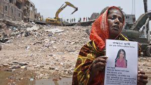 Nainen pitelee kadonneen tyttärensä kuvaa romahtaneen tehdasrakennuksen raunioiden edustalla.