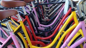 Värikkäitä polkupyöriä pyörätelineessä.