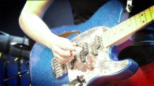 Nainen soittaa kitaraa.