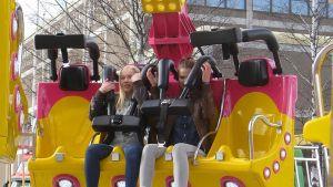 Kaksi tyttöä huvipuistolaitteessa.