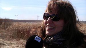 Janna Räisänen, taustalla kaksi tuulivoimalaa.