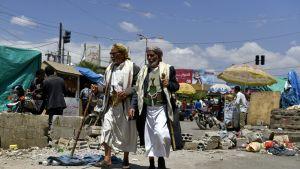 Kaksi miestä kävelee kadulla Sanaassa