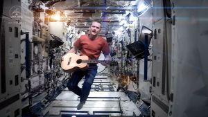 astronautti leijuu kitaran kanssa avaruusasemalla