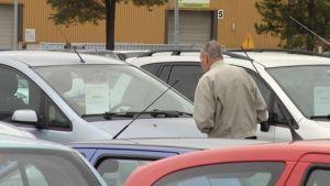Mies katselee kesäautoa autokaupan pihalla.