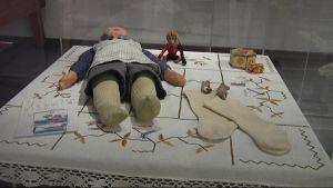 Lahden historiallisen museon vitriinissä on leluja, puuterirasia ja sukat.