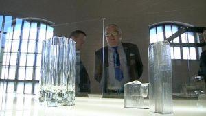 Kyösti Kakkonen katselee Tapio Wirkkalan lasimuotoilua lasin takaa