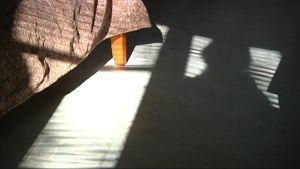Ihmisen varjo lankeaa lattiaan.