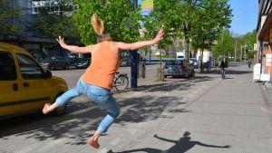 Nainen hyppää ilmaan kadulla.