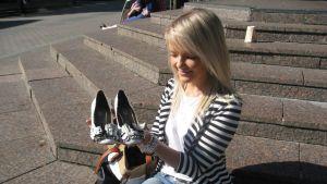 Nainen istuu portailla kengät kädessä.